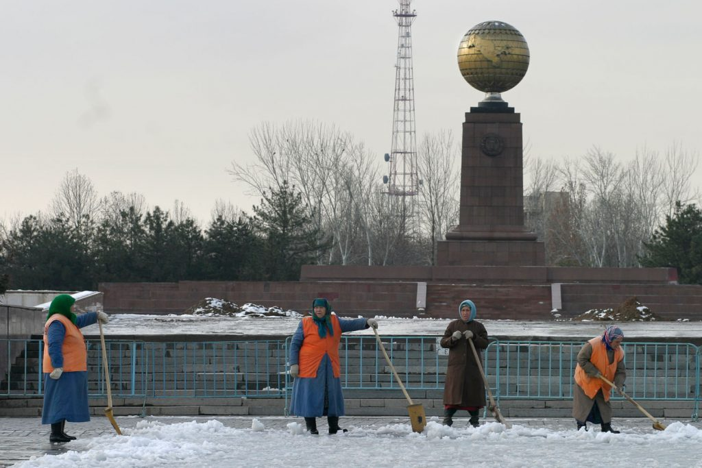 TASHKENT, UZBEKISTAN - MARCH, 2005: Street sweepers clear the snow infront of Independence Square where the largest Lenin statue in the USSR has been replaced with a brass globe with an oversized map of Uzbekistan on it.(Photo by Christopher Herwig)